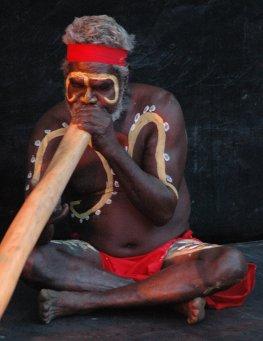 Aborigine blässt auf seinem Didgeridoo