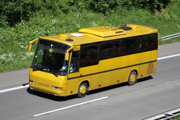 Gelber Bus auf der Autobahn.