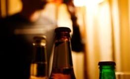 Ein sitzt im Hintergrund und trinkt Alkohol