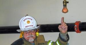 Feuerwehr-Chef Lynn Owens, zeigt auf die Glühbirne, die seit 110 Jahre ihren Dienst verrichtet.