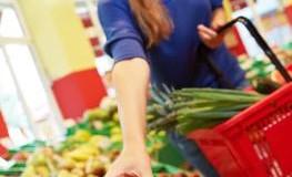 Frau greift im Supermarkt nach einem Apfel aus dem Obstregal
