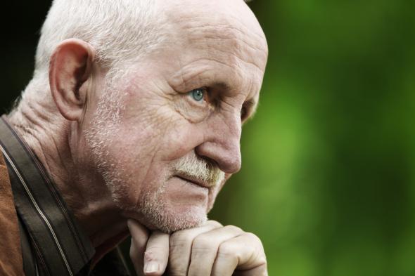Alter Mann schaut pessimistisch in die Ferne.
