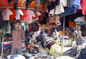 Markt in Bangladesch - junger Mann verkauft Altkleider aus der ersten Welt als Second-Hand-Ware