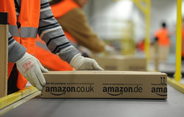 Amazon-Logistikzentrum - Mitarbeiter von Amazon macht ein Paket für den Versand fertig.
