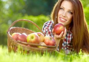 Junge Frau mit einem Korb voller Äpfel
