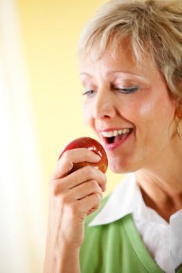 Ältere Frau möchte in einen Apfel beißen