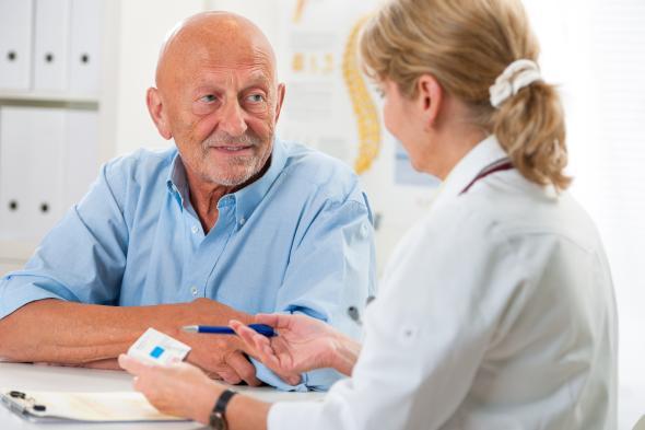 Ärztin erklärt dem Patienten wie er das Medikament einnehmen muss.