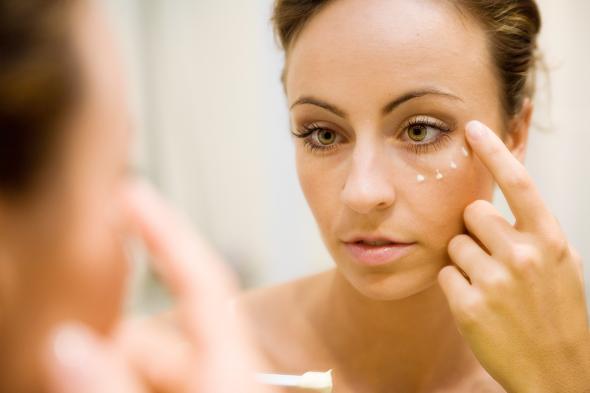 Augenringe - Junge Frau reibt sich mit der Hand eine Creme unter die Augen.