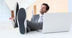 Mann hat seine Füße auf dem Schreibtisch.