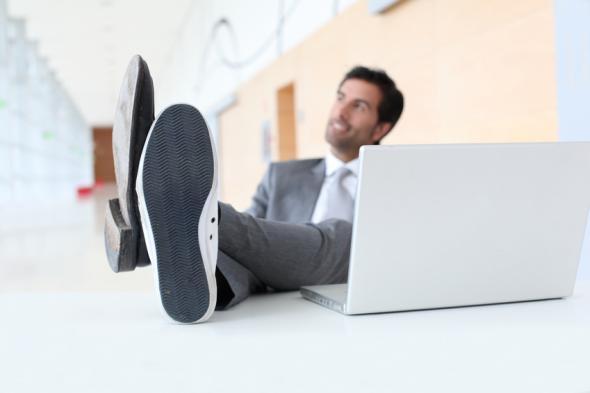 Mann hat seine Füße mit unterschiedlichen Schuhen auf dem Schreibtisch.