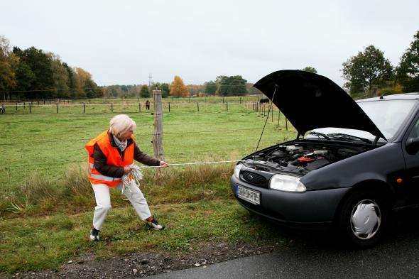 Eine Frau versucht mit einem Seil ihr Auto abzuschleppen.