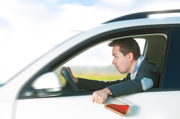 Ein Mann hinter dem Steuer eines Fahrzeuges, in der linken Hand hält er ein Flasche Whisky.