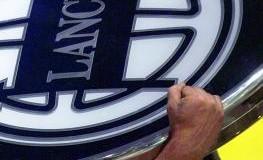 Handwerker trägt das Logo von Lancia auf der Schulter