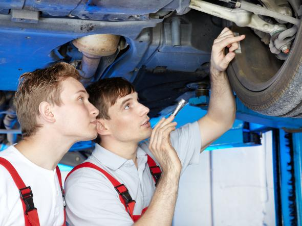 Der Kfz-Meister erklärt dem Auszubildenden was an dem Fahrzeug gemacht werden muss.