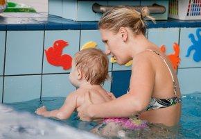 Baby schwimmt unter Anleitung von Schwimmlehrern