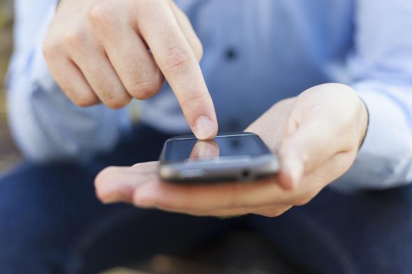 Ein Mann tippt auf seinem Smartphone mit dem Finger rum.