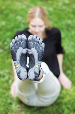 Junge Frau zeigt ihre neuen Barfußschuhe von Vibram
