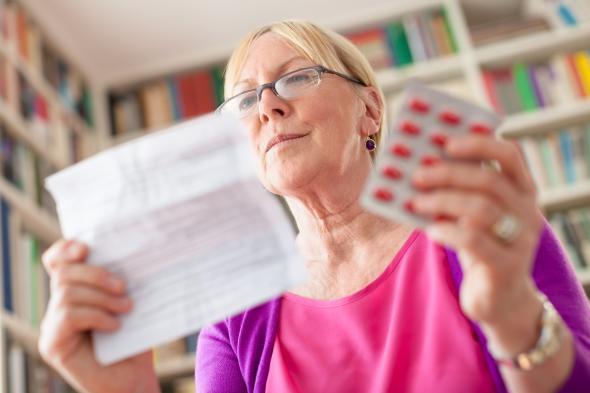 Seniorin liest den Beipackzettel von einem Medikament.