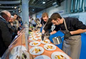 Köche bei der Arbeit - Teller mit Fisch werden trapiert