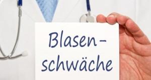 """Arzt hält ein Schild mit der Aufschrift """"Blasenschwäche"""""""