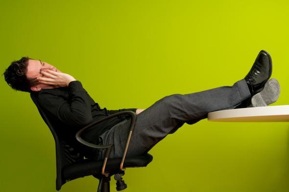 Ein Mann sitzt in seinem Bürostuhl zurückgelehnt mit Füßen auf dem Schreibtisch und schläft.