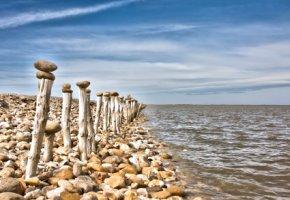 Camargue - Holzpfähle mit Steinen entlang der Küste