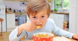 Cerealien: Ein Bub isst zum Frühstück Cornflakes.