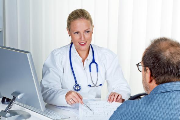 Ärztin erklärt einem Patienten den Therapieplan.