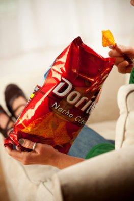 Bewegungsmangel und fettes Essen: Couch-Potato - auf dem Sofa liegen und Kartoffelchips essen