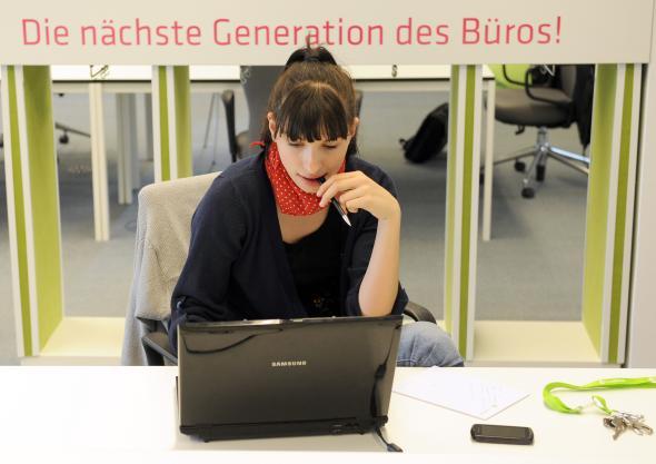 Junge Frau arbeitet an ihrem gemieteten Arbeitsplatz