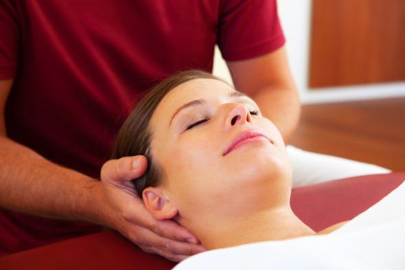 Therapeut behandelt eine Patientin mit der Cranio-Sacral-Therapie.