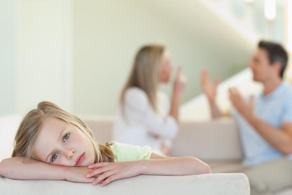Trauriges Mädchen - im Hintergrund streiten die Eltern.