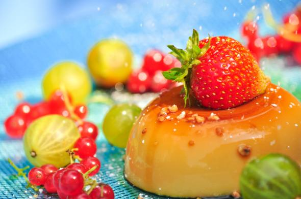 Leckeres Dessert - Panna Cotta mit Karamellsoße und Früchten.