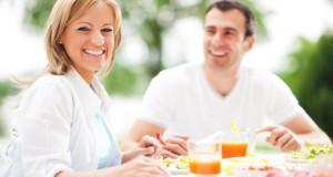 Pärchen mittleren Alters sitzt draußen und frühstückt gesunde Dinge