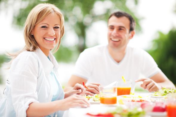 Pärchen mittleren Alters sitzt draußen und frühstückt gesunde Dinge.