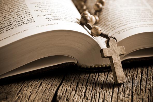 Aufgeschlagene Bilbel und eine Kette mit Kreuz.