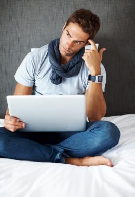 Ein Mann mittleren Alters sitzt nachdenklich vor seinem Laptop