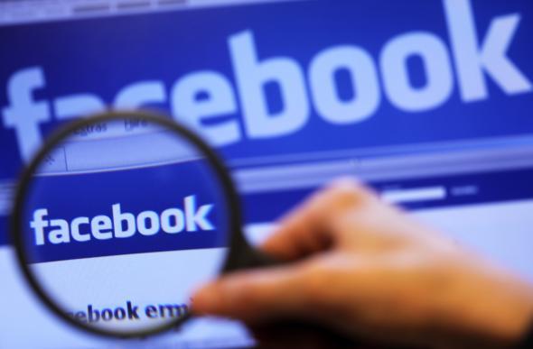 """Eine Lupe vor einem Bildschirm mit dem Schriftzug """"Facebook"""""""