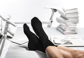Füße mit schwarzen Socken auf dem Tisch hochgelegt