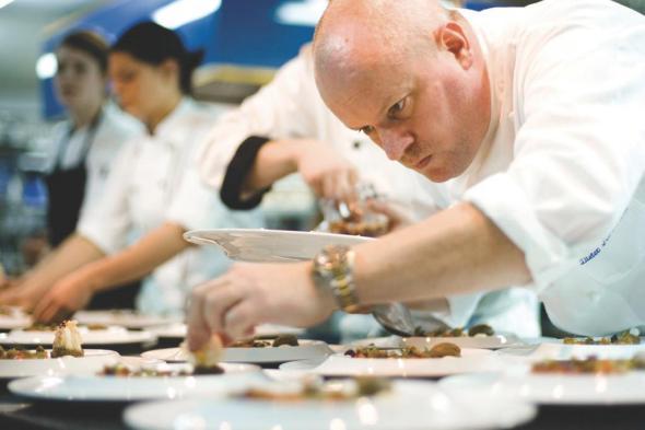 Dieter Koschina trapiert einen Teller mit Köstlichkeiten.