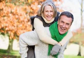 Älteres Ehepaar - der Mann nimmt seine Frau huckepack.