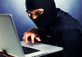 Ein internetkrimineller bei der Arbeit am Laptop