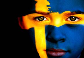 Ein Junge mit der Schwedischen Fahne im Gesicht