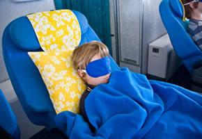 Ein Junge schläft auf dem Flug
