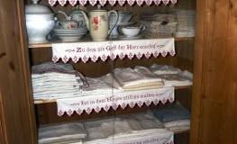 Ein typischer Aussteuerschrank gefüllt mit Textilien und Geschirr