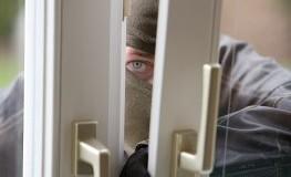 Einbrecher an einem gekippten Fenster