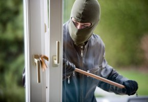Einbrecher hebelt ein Fenster mit dem Brecheisen aus