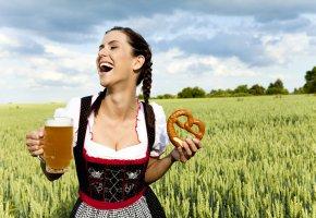 Eine Frau im Dirndl mit einer Maß Bier