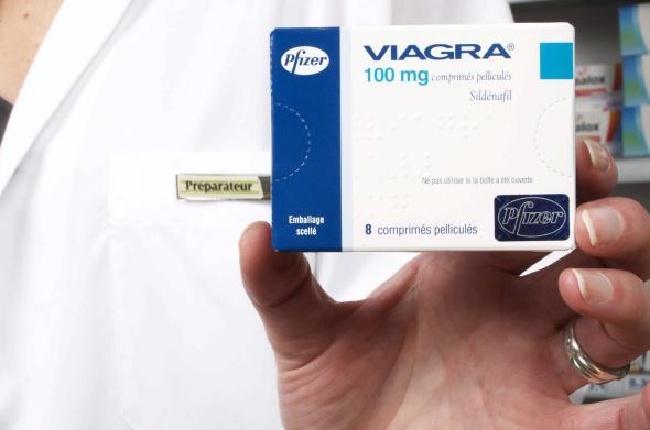 Apothekerin hält eine Schachtel Viagra in der Hand.