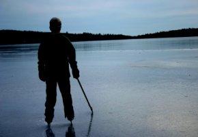 Jugendlicher Eishockeyspieler steht auf einem See in Kanada